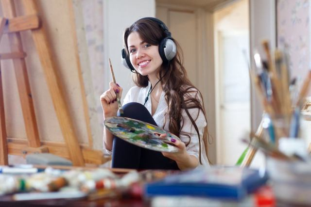 Long-haired-woman-in-headphones-paints-with-oil-colors