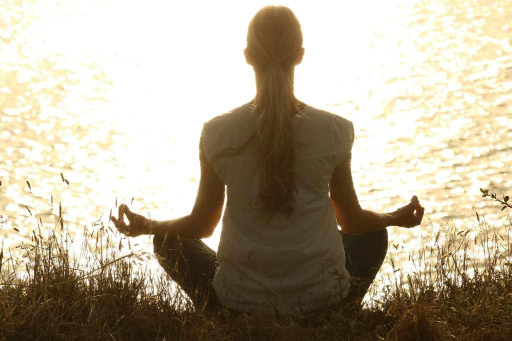 woman meditating sunset