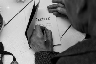 Hendrik Mentz signing a copy of 'Enter' purchased by Louise Coetzer and Oscar O'Ryan | photo credit: Oscar O'Ryan