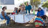 The Birds of Xairu selling their homemade produce on the braak (village green) of Suurbraak