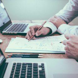 Zwei Hände schreiben ein Konzept auf einem Blatt Papier zwischen zwei Laptops.