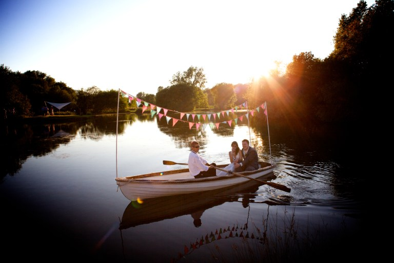 A picture of a couple on a small rowing boat on a lake.