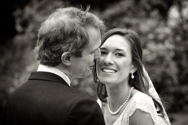 black and white image of smiling newlyweds in a park in Surrey