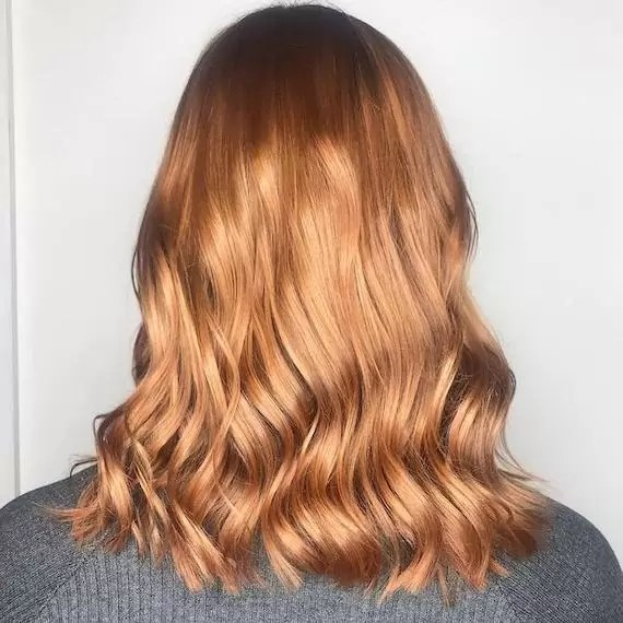 Photo of the back of a woman's head showing red hair with copper highlights, created using Wella Professionals
