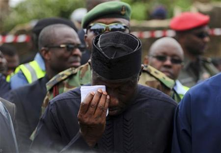 Nigeria's President Goodluck Jonathan wipes a tear after he arrived to inspect the site of a plane crash in Lagos