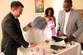 The bride Zanele Ndlovu signs a marriage certificate while the groom Jimmy Fox (left) and a pastor witness during a wedding held at a local hospital in Bulawayo yesterday