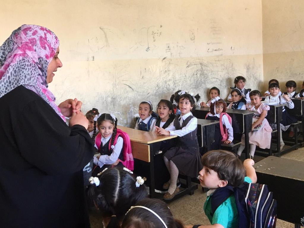 A teacher greets students on the first day of elementary school in Mosul, where regular classes have started for the first time since ISIS took over the city three years ago. Hundreds of schools were damaged or destroyed in the fighting to take back Mosul. Others that have reopened lack books and basic supplies.