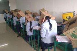 India: Student wear boxes on their head during exams to prevent cheating