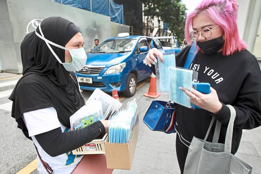 A seller selling face mask for rm1 per piece and cloth mask for rm5 per piece at the Pavillion zebra crossing. They can earn up till rm90- rm100 perday from 12pm to 10pm. NORAFIFI EHSAN / The Star.
