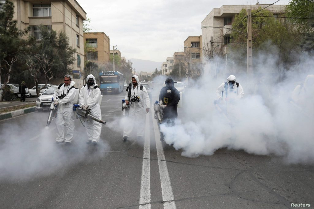 Members of firefighters wear protective face masks, amid fear of coronavirus disease (COVID-19), as they disinfect the streets, ahead of the Iranian New Year Nowruz, March 20, in Tehran, Iran March 18, 2020. Picture taken March 18, 2020. WANA (West Asia News Agency)/Ali Khara via REUTERS ATTENTION EDITORS - THIS PICTURE WAS PROVIDED BY A THIRD PARTY     TPX IMAGES OF THE DAY
