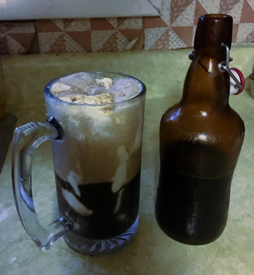 mug with ice cream and beer in it beside an unstoppered bottle