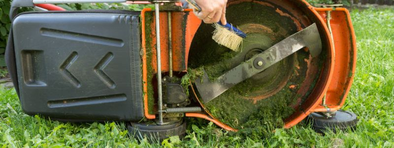 man cleaning lawn mower