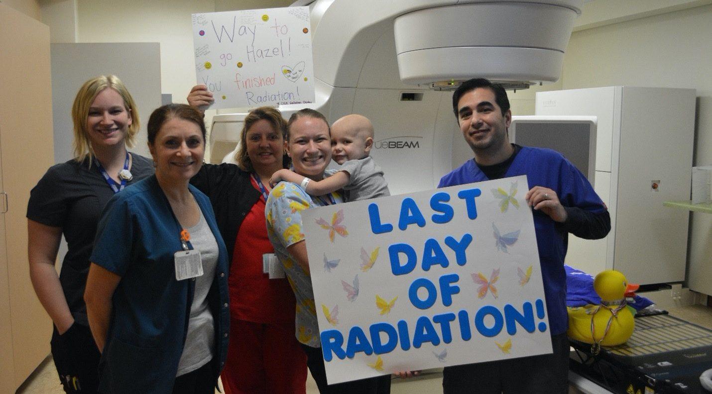 Team of nurses and family celebrating last day of radiation