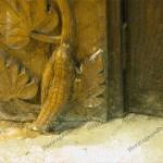 caterpillar carving at foot of door