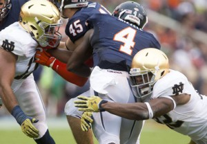 Notre Dame's Elijah Shumate (22) tackles Virginia's Taquan Mizzell (4) during the second half of the Fighting Irish's 34-27 win over Virginia Saturday, September 12, 2015 in Charlottesville. (SBT Photo/BECKY MALEWITZ)