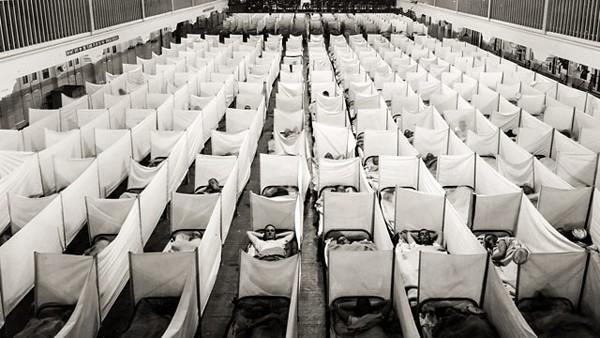 Zone de couchage de la caserne principale, Naval Training Station à San Francisco avec des écrans anti-éternuements érigés par mesure de précaution contre la propagation de la grippe, 1918, photographie du US Naval History and Heritage Command. L'agrandissement est une photographie prise à Langres (Haute-Marne), 1918. Pavillon de la grippe dans un camp militaire, Washington, Library of Congress.
