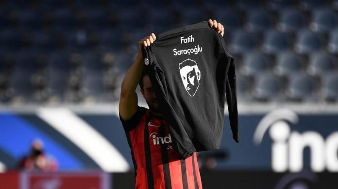 Amin Younes holds up a t-shirt commemorating the Hanau victims