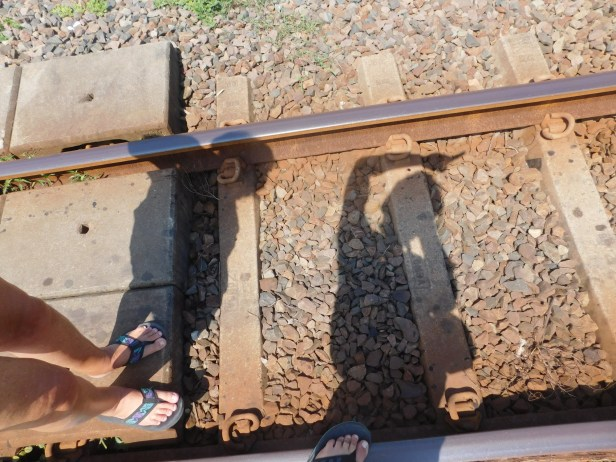 Shadows of two people standing on the railway line.