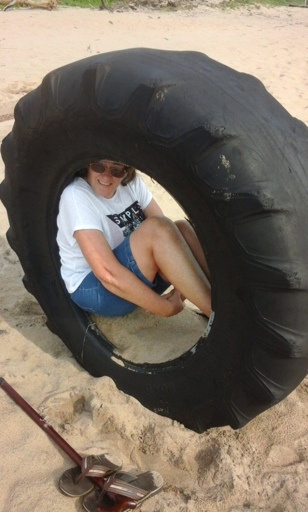 Me, at Mtwalume Beach, seeking shelter against the sun in the discarded tyre of a bulldozer