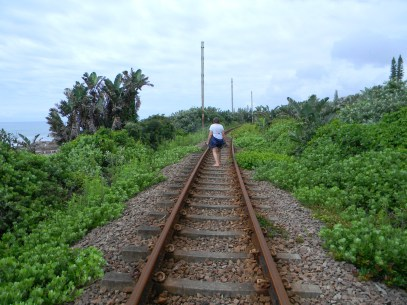 Walking along the railway line to the beach in the background