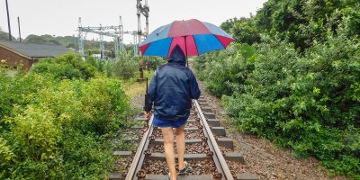 Woman walking along the railway lines in rainy weather