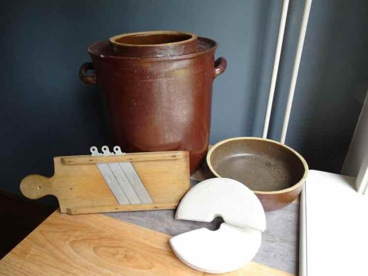 Zuurkoolpot met koolsnijder en verzwaringsstenen.