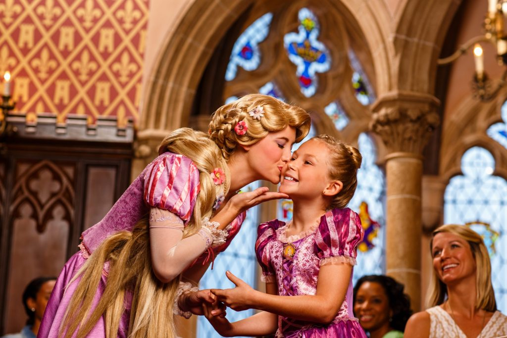 Disney Princess Rapunzel kisses the check of a little girl who is smiling ear to ear and dressed the same as Rapunzel. WDW Character Dining Lifestyle Shoot. 2013. Photographer: Melanie Acevedo
