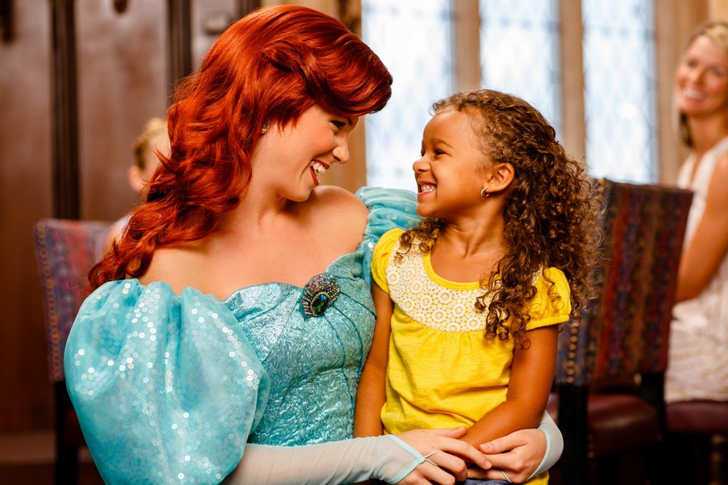 Disney Princess Ariel sits with a young girl while dining at Walt Disney World. Here is the photo info: WDW Character Dining Lifestyle Shoot. 2013. Photographer: Melanie Acevedo