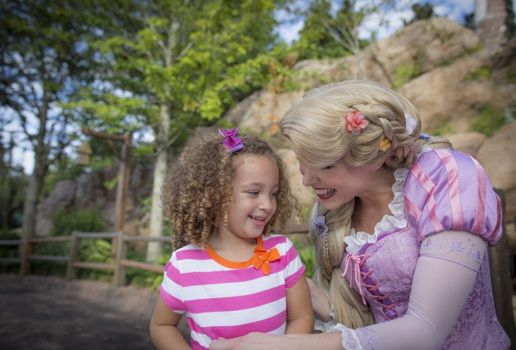 Disney Princess Rapunzel smiles at a young guest while giving her a hug.