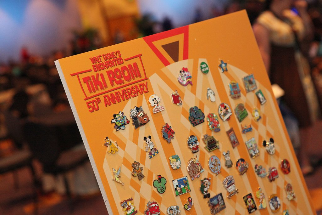 Walt Disneys Enchanted Tiki Room 50th Anniversary pin trading board is on display with several bright colored disney pins.