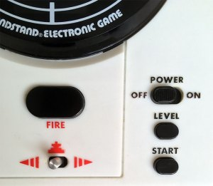 Invader from Space: Image shows the bottom right section of the unit containing the power switch, a level selection button and the start button. Toward the centre is the fire button and directly underneath a left/right toggle switch for movement of the player's ship.