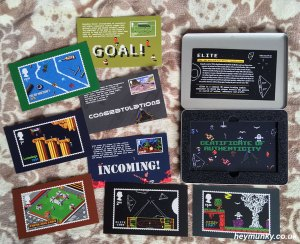 An above view of the various mounts for the video game stamps along with the presentation tin. Included game depictions are: -Micro Machines, Sensible soccer, Wipeout, Lemmings, Worms, Populous, Elite and Dizzy.