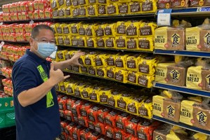Staff stocking bread in grocery aisles