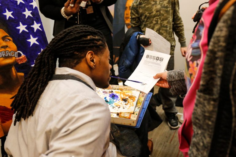 Students interact with mouth painter Antonio Davis during his talk and demonstration of his art.
