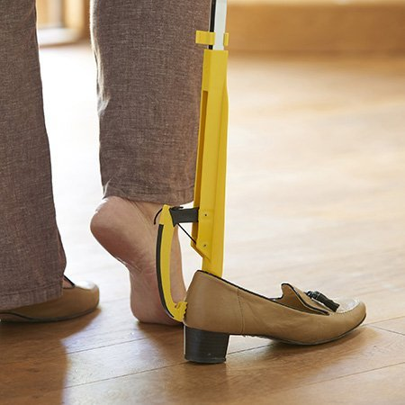 Shoe Helper Reacher Grabber holding shoe in place and the shoe horn helps slide your feet into the shoe. Can be used from a standing or sitting position, without the need to bend.