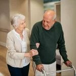 Elderly woman helping her husband using a walking frame before or after surgery