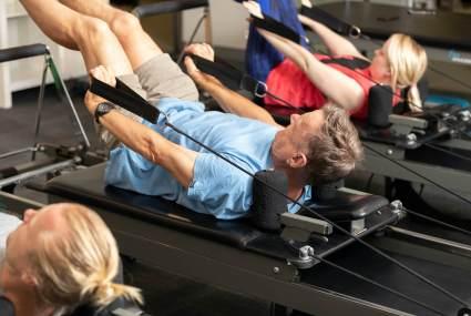 man using pilates reformer for exercise