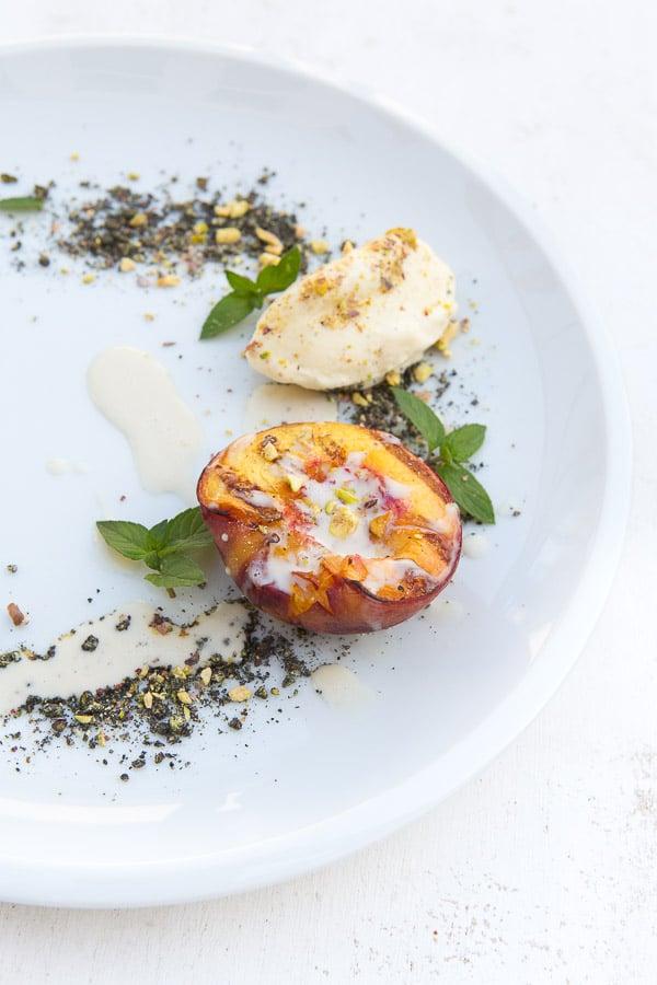 Gegrillter Pfirsich mit Vanille-Kardamom-Eis, Pistazien und Mandelcrème
