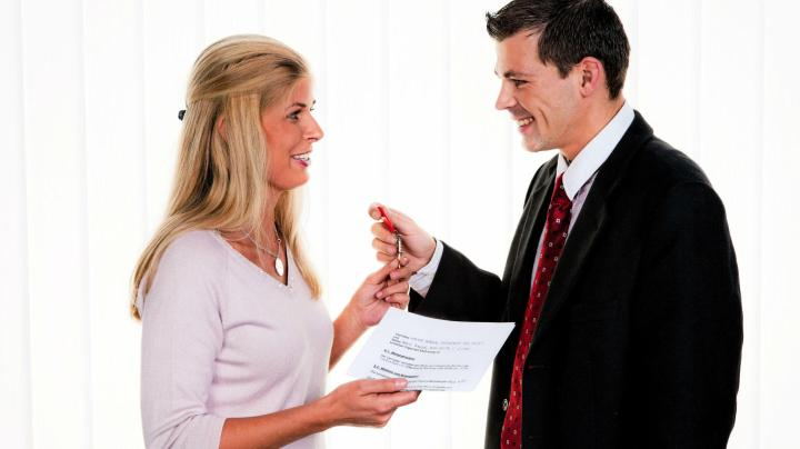 Landlord handing keys to tenant with documents