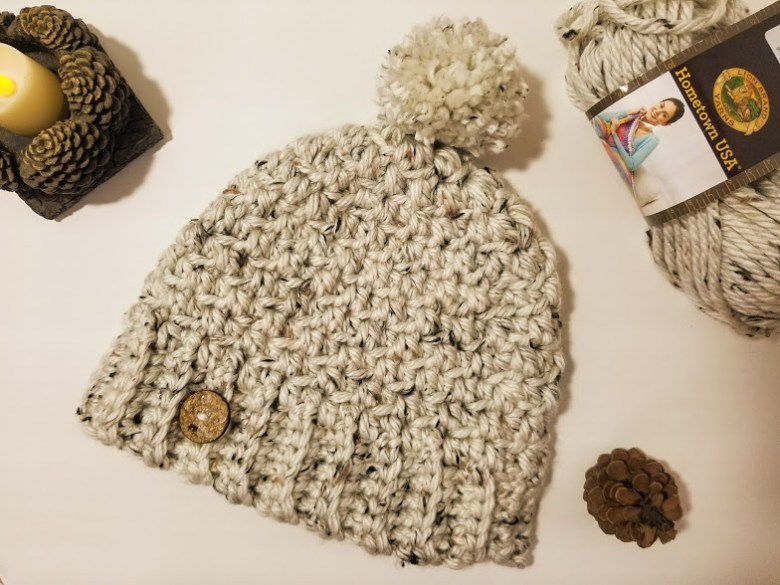 aspen tweed hat. chunky linen colored hat laying flat on a table. Has a pompom on top