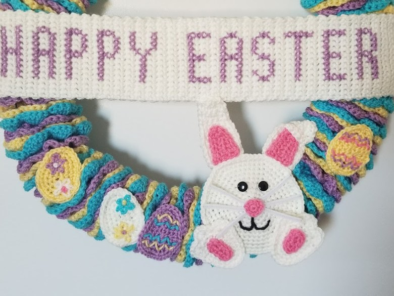Easter wreath close up of bunny applique, eggs and banner