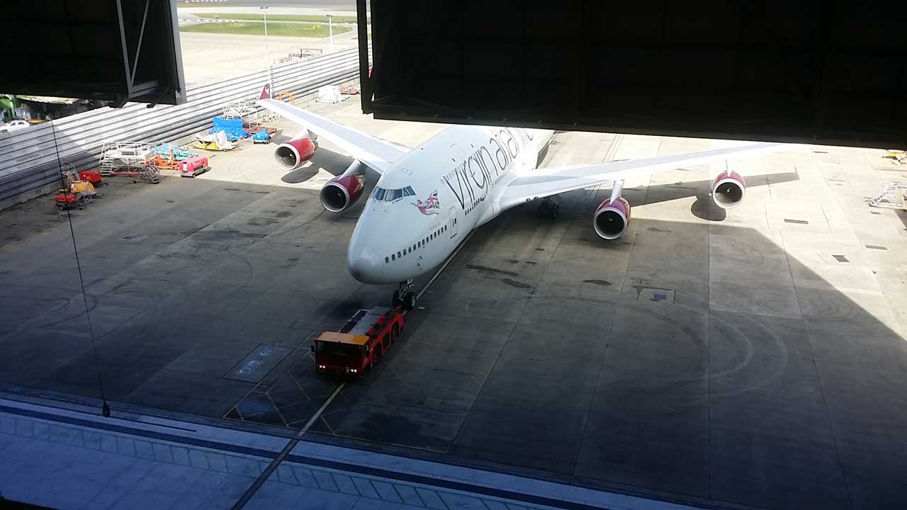 Looking down from the roof space at a Boeing 747 being towed in by the fork truck. Gallery