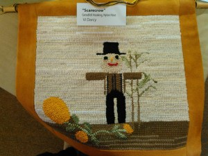 A Grenfell-style mat by ____ offered at Artful Threads as a raffle gift.