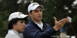 Coach helping high school golfer