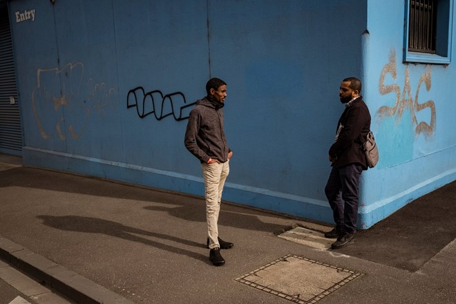 Community health worker Ahmed Dini and colleague Nor Shanino discuss a proposed call centre to help with the mental health and concerns of residents in Flemington and North Melbourne housing commission flats. Photograph: Christopher Hopkins/The Guardian