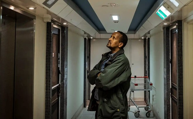 Hamdi Ali, a resident at the 141 Nicholson Street flats, waits for the elevator on the sixth floor. Photograph: Christopher Hopkins/The Guardian