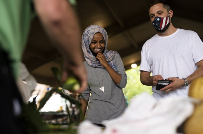Ilhan Omar campaigns with her husband Tim Mynett at the Richfield Farmers Market on 8 August 2020 in Richfield, Minnesota(Getty)