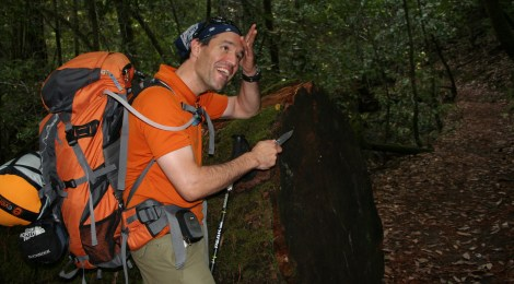 James Temple backpacking the Skyline-to-the-Sea trail and pretending to cut through a massive log with his pocket knife.