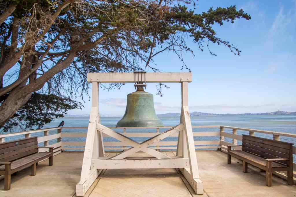green patina bell hanging from a white wood structure on a platform next to the water