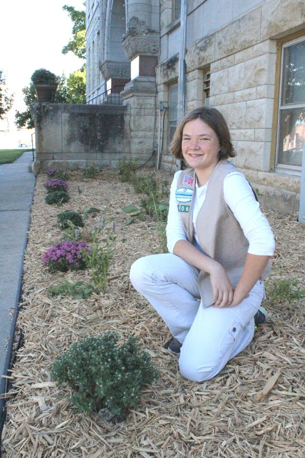 Nicole Sanders of Peabody poses with the landscaping project she completed on the southwest corner of the Marion County Courthouse during September. She took on the project with the hope of earning a Silver Award, the highest award for a Cadette in Girl Scouts.